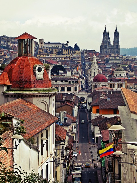 A photograph taken from a high location in the historic center of Quito, Ecuador, looking down on a city street and buildings in the distance.